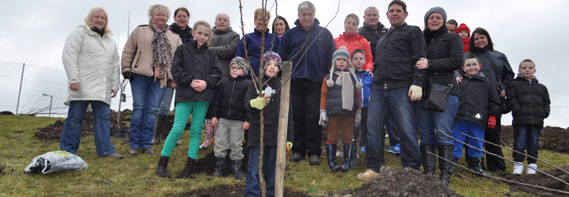 Community Group planting a tree in an orchard