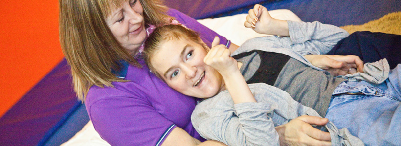 Young girl with disabilities and her carer that is used on the front cover of our leaflet